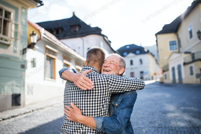 An adult hipster son and his senior father in town, hugging.