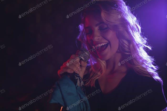 Fröhliche Sängerin, die im beleuchteten Nachtclub auftritt