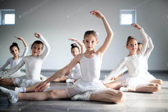 Gruppe von kleinen Ballerinas Mädchen tun Übungen in der Tanzschule