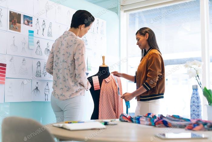 Diverse female fashion designers working together working on garment on dressmaker model
