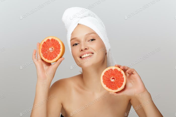 Portrait of young cheerful woman without makeup with white towel