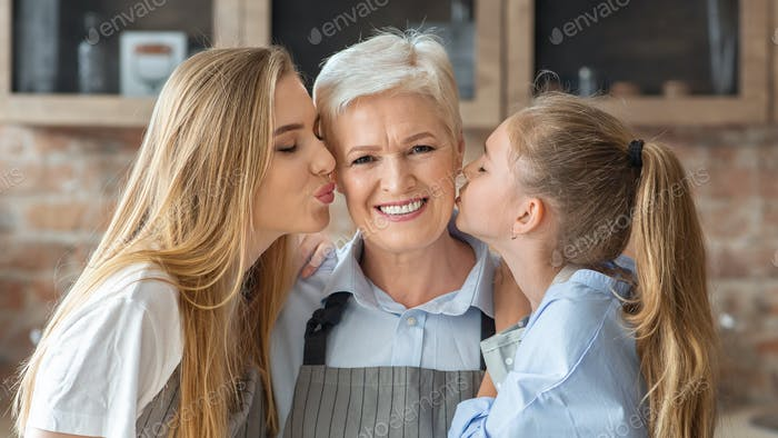 Portrait of mom and daughter kissing granny