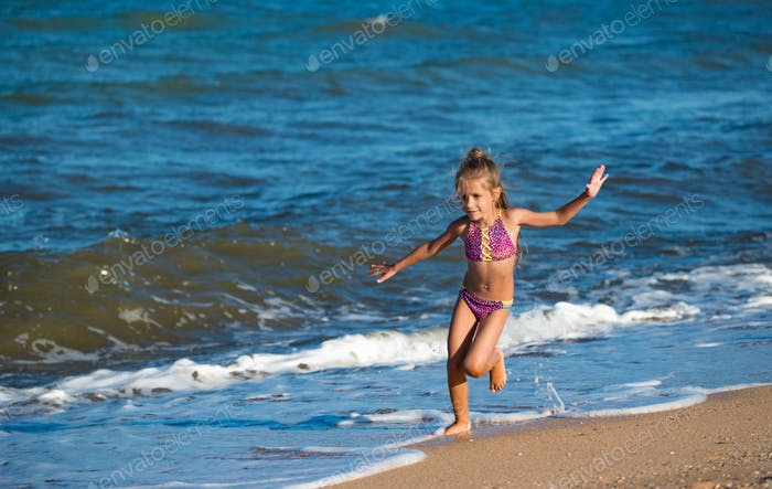 Happy little girl runs along the sandy shore
