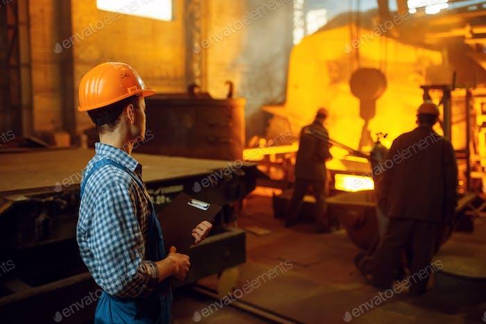Master looks on steelmaking process in furnace