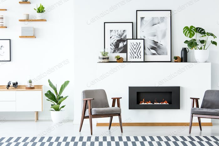 Black fireplace between grey armchairs in apartment interior wit