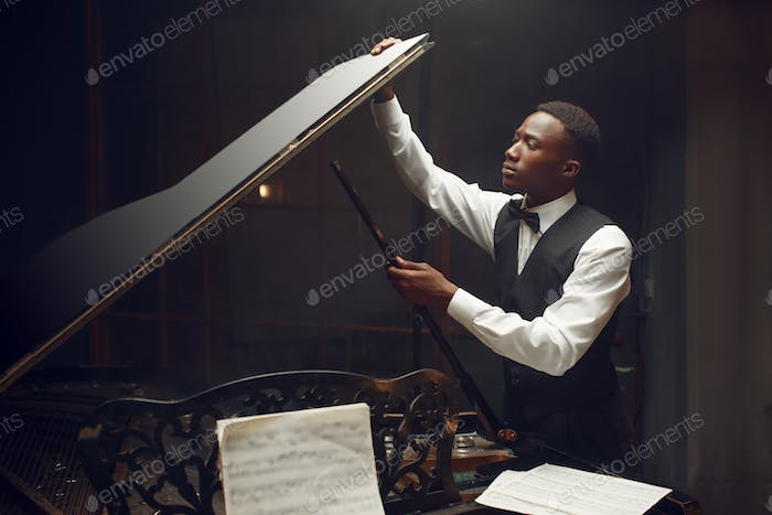 Ebony player tuning grand piano on the stage