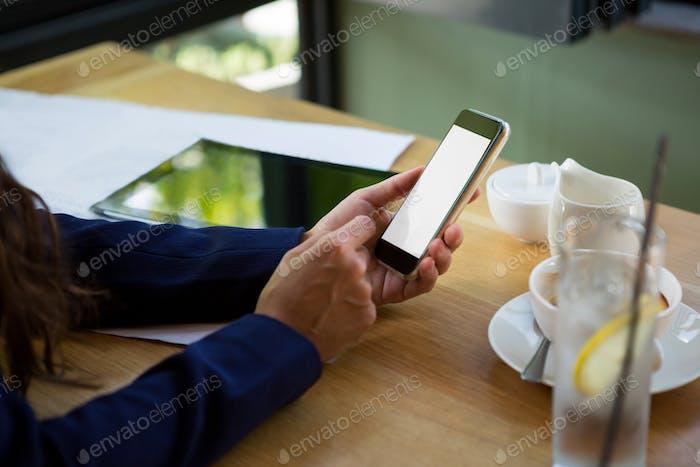 Mujer Uso teléfono Móvil en la cafetería