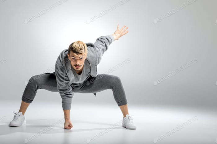Young athletic male dancer in sportswear posing with fist hitting floor