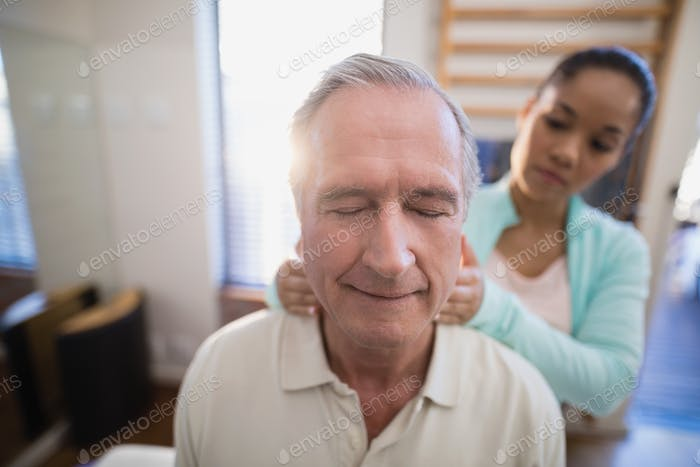 Senior male patient with eyes closed receiving neck massage from female therapist