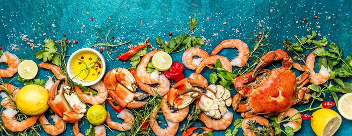 Baner. Fresh raw seafood - shrimps and crabs with herbs and spices on turquoise background