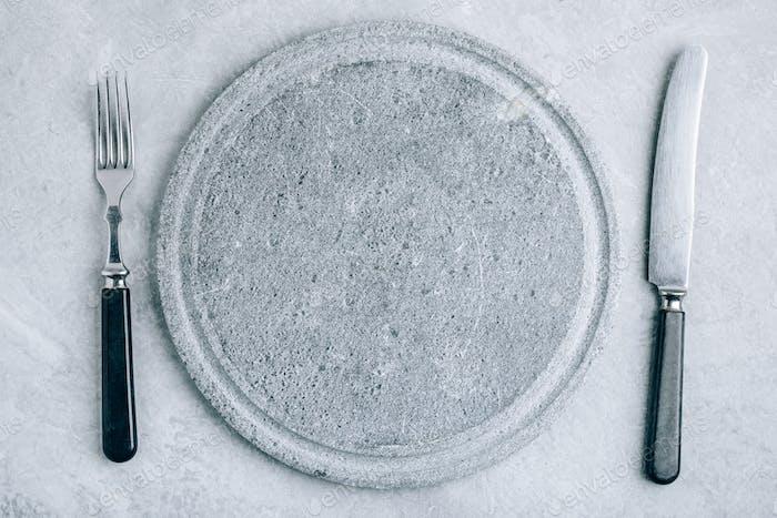 Leere runde Steinplatte oder Teller mit Gabel und Messer auf grauem Beton Hintergrund Oberfläche Hintergrund