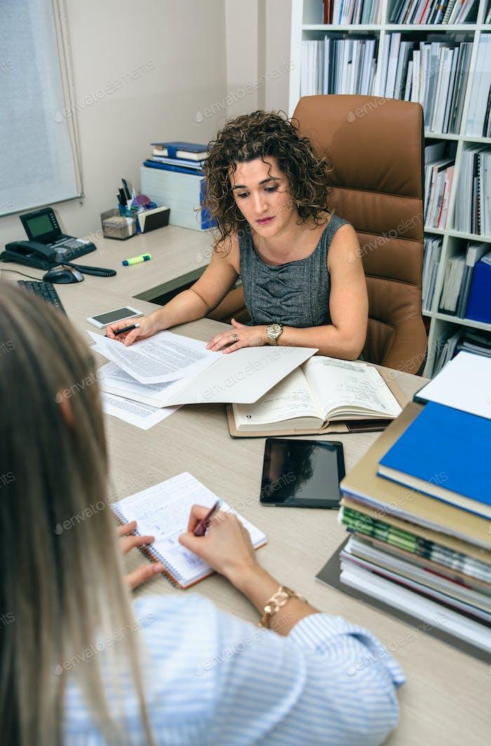 Geschäftsfrau und Sekretärin arbeiten im Amt mit Dokumenten
