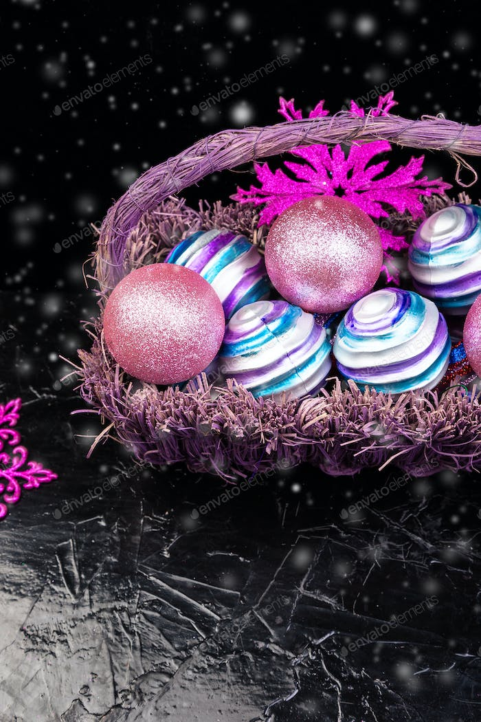 Christmas balls in purple basket on black background with snow. Decorative snowflakes.