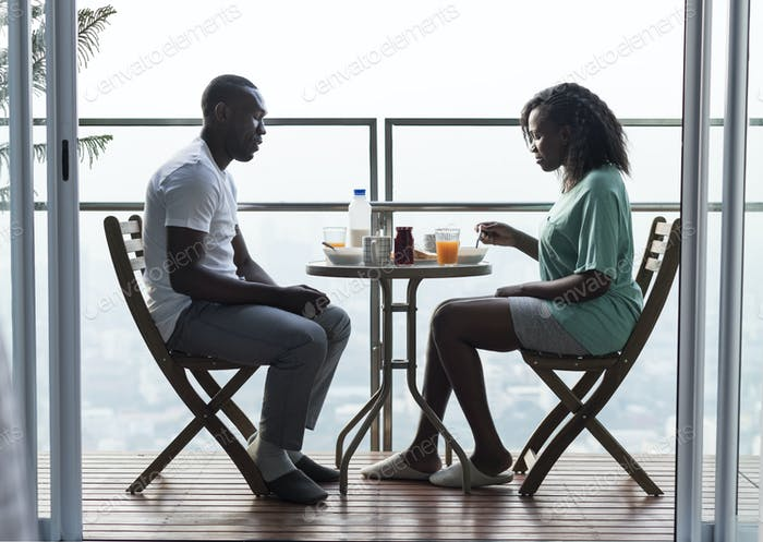 Couple having breakfast together at the balcony