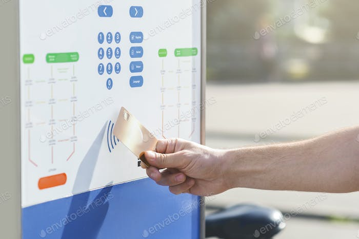 Man with credit card using contactless pay system on rent terminal