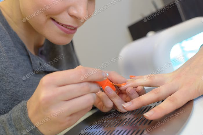 Beautician painting customer's nails