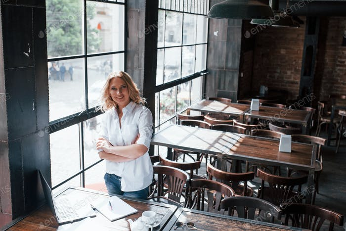 Standing with arms crossed. Businesswoman with curly blonde hair indoors in cafe at daytime