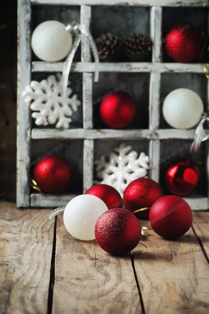 Weihnachtskarte mit Kugeln auf dem Holztisch