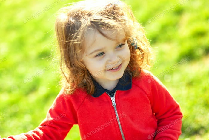 Cute toddler looking away on green grass.