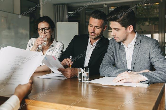 Gruppe von kaukasischen Arbeitgebern in formeller Abnutzung sitzen am Tisch in