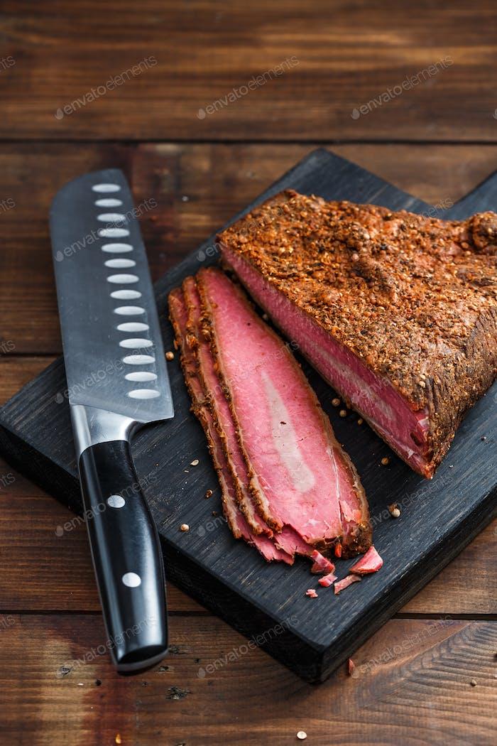Rindfleisch Pastrami in Scheiben geschnitten auf Holzbrett