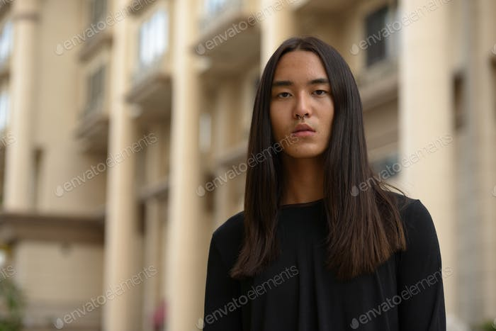 Portrait of young Asian man with long hair