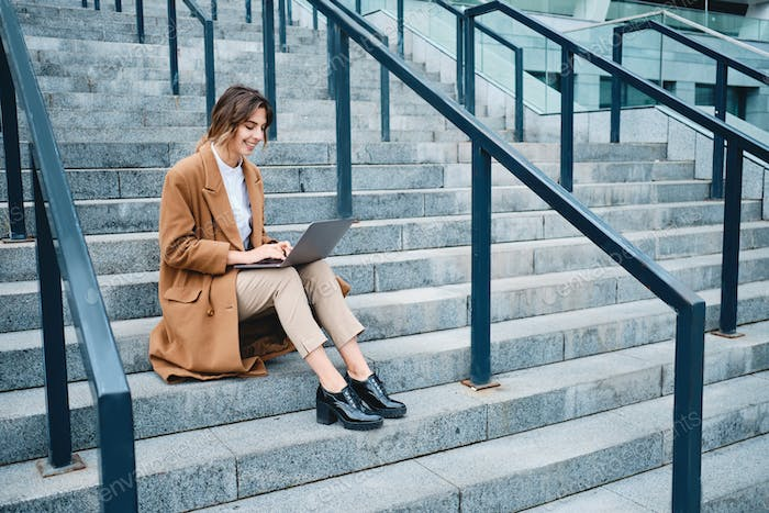 Young pretty smiling businesswoman in coat happily working on laptop on stairs outdoor