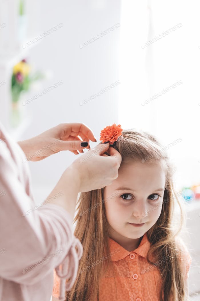 Mother clipping a hair clip with red flower