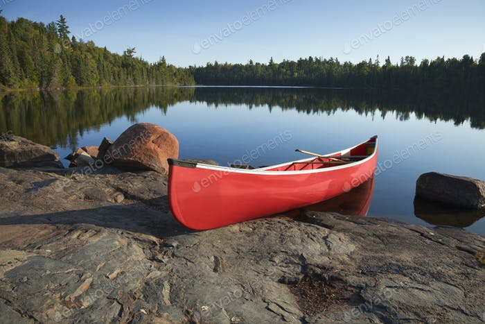 Red Canoe on Rocky Shore of Calm Lake with Pine Trees