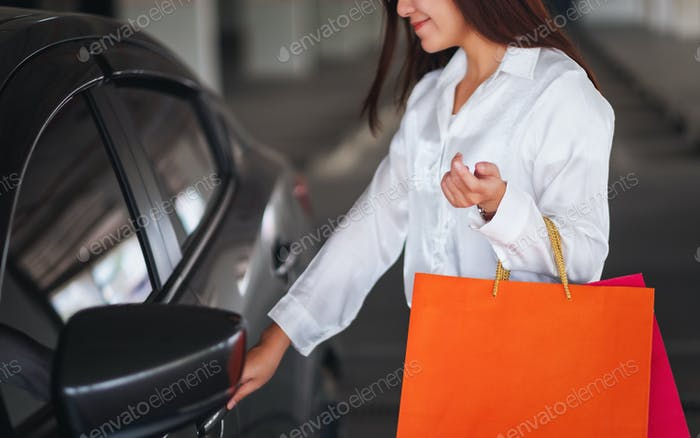 A beautiful woman holding shopping bags while opening car door in the mall parking lot