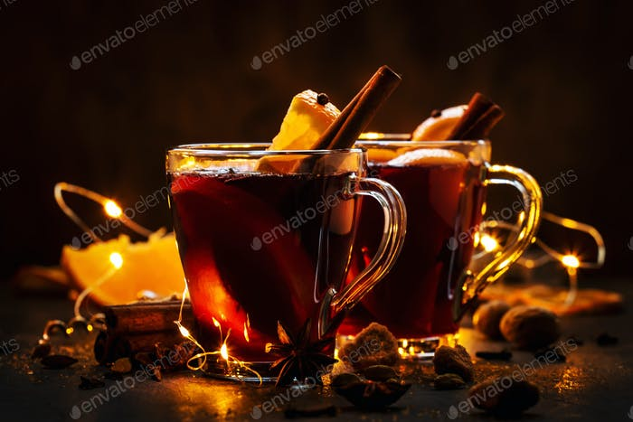 Christmas mulled red wine with spices and fruits on wooden rustic table