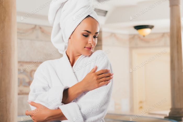 young woman in white terry robe with towel on head