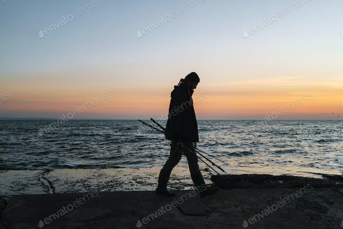 Silhouette of man fisherman wearing coat, holding rod