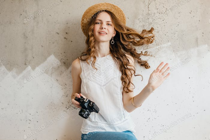 young pretty smiling happy woman in straw hat holding vintage photo camera, long curly hair