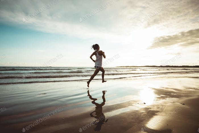 Woman running on sunset beach
