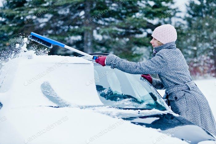 Frau Entfernen Schnee aus einem Auto mit einem Besen