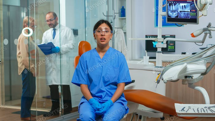 Dental assistant looking at camera speaking with patients