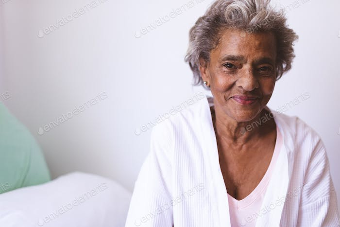 Portrait of happy senior mixed race woman smiling while sitting on bed at nursing home