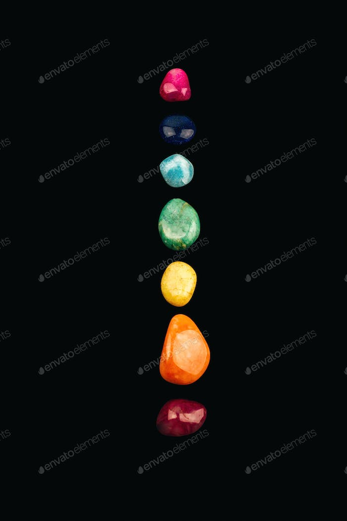Chakra stones, crystals in a row on black background