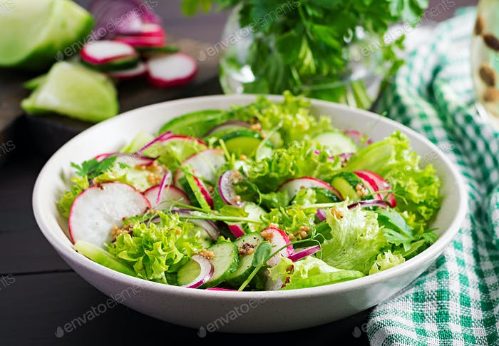 Healthy vegan food. Vegetarian vegetable salad of radish, cucumbers, lettuce  and red onion.