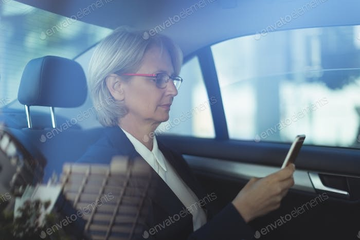 Businesswoman using phone in car