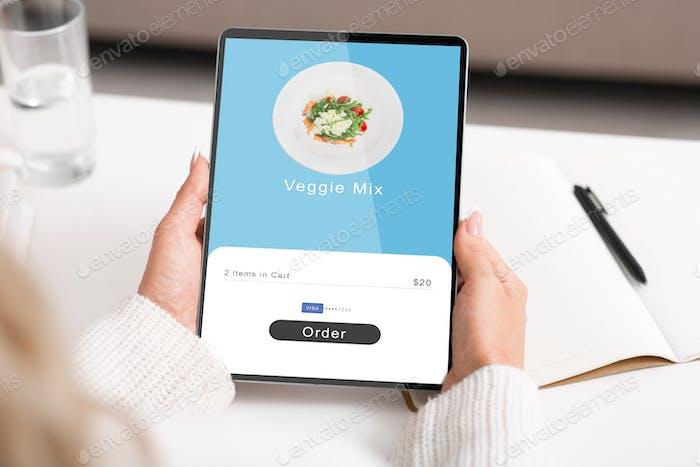 Moderne Technik, mobile App und trendiger Vegetarismus. Frau bestellt Essen auf Tablette