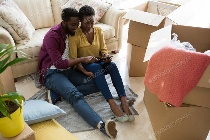 Couple using digital tablet while relaxing in new house