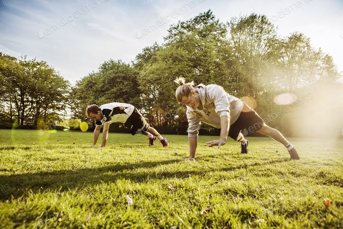 Young men doing push-ups on grassy field on sunny day