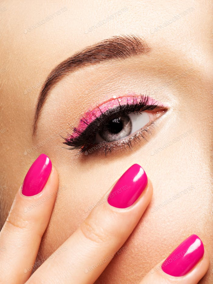 Nahaufnahme Frau Gesicht mit rosa Nägeln in der Nähe der Augen.