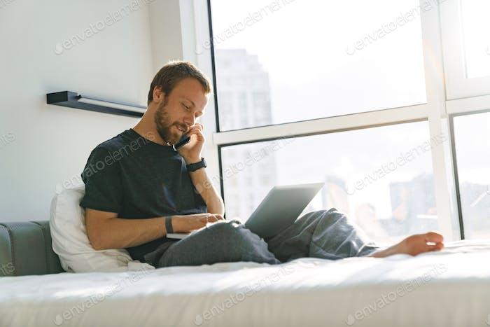 Foto von zufriedenem Mann im Gespräch auf Handy während der Arbeit mit Laptop
