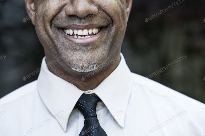 The face of a smiling businessman in a shirt and tie, nose and chin,