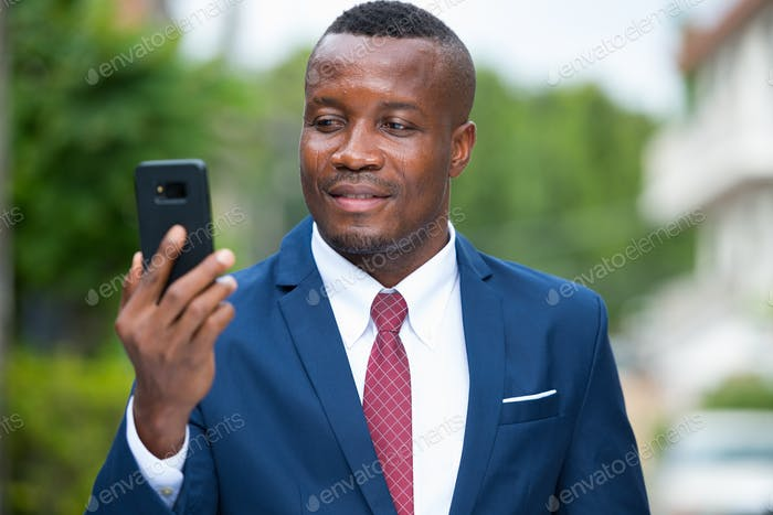 Young African businessman with mobile phone outdoors