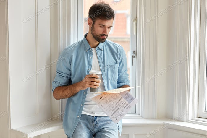 Horizontal shot of serious unshaven man holds printed statistics documents, analyzes graphs and char