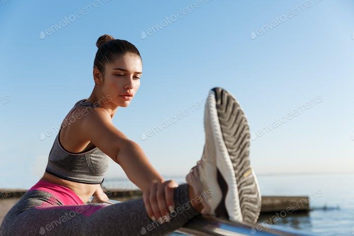 Primer plano de la atractiva deportista sosteniendo la pierna en la cuerda de mano, estirándose en el paseo marítimo